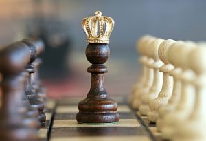 A dark brown chess piece with a gold crown sitting on top, resembling a queen.