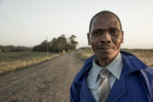 Older man with brown skin standing by a road